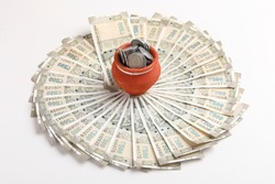 Clay piggy bank pot with five hundred indian rupees bank note on white background