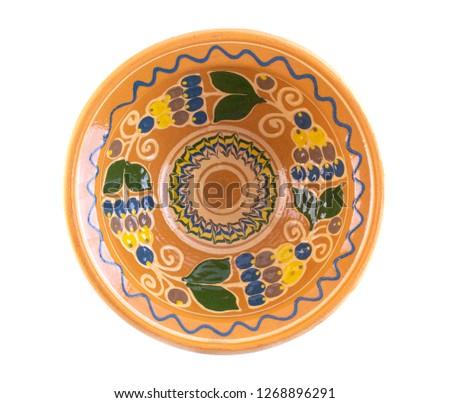 clay plate painted with flowers and fruits  poured on a white background top view #1268896291
