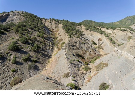 Clay ravines at the foot of the mountains. On the slopes of ravines one can see the  structure of sedimentary rocks. Crimea, sunny day in September.