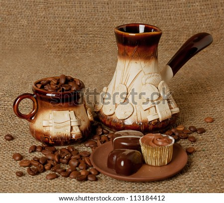 Clay set for coffee with chocolate sweets on the sack background