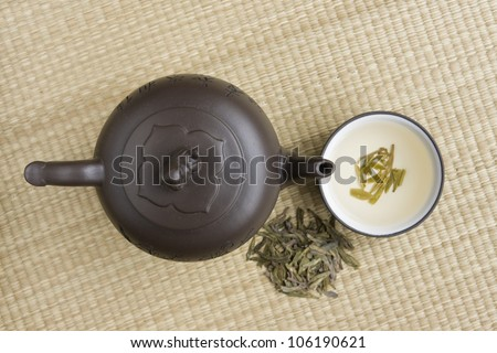 Clay teapot and a cup of green tea on a bamboo mat