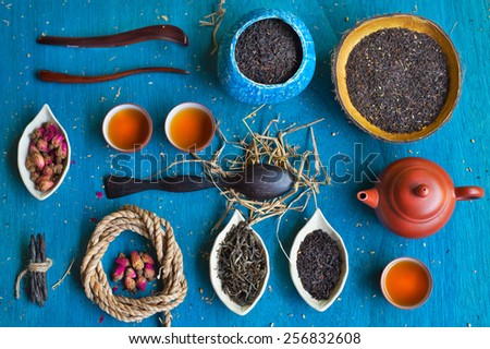 Clay teapot, three teacups, coil of rope, rosebuds, three wooden spoons, two handmade coconut bowls and three saucers in the form of petals with different sorts of tea on blue wooden background.