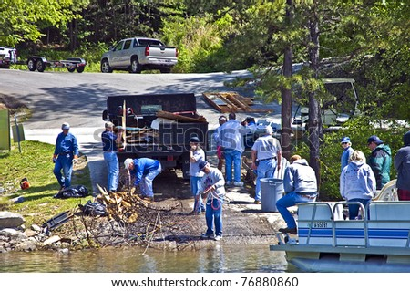 CLAYTON, GA - MAY 6: A group of volunteers clean tornado debris on May 6, 2011 in Rabun County, Lake Burton, Clayton, GA. It was hit with the worst tornado to ever hit the area.