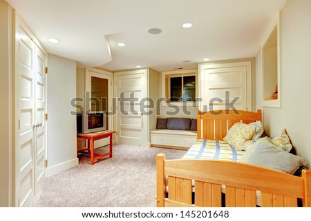 Clean and bright minimalistic basement bedroom with window bench and many doors.