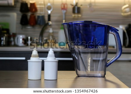 Clean and Dirty filters for cleaning drinking water on the kitchen table. Purification of drinking water at home #1354967426