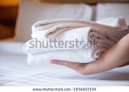 Clean and fresh towels are holding by woman's hands, putting down on bed. Focus on stack of towels. Foto stock ©
