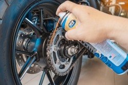 clean and lube a motorcycle chain with oil Spray in Motorcycle garage, service and maintenance concept