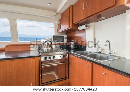 Clean and modern galley/kitchen of a private sailing catamaran with wooden cupboards, sink, oven, microwave and kettle, with Mediterranean sea view from the windows.  Stockfoto ©