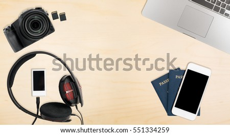 Clean and tidy wooden desk with equipment ready for travel including camera, laptop, phone, music player and passports