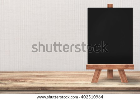Clean blackboard with easel on top of wooden table with grey wall background. For the idea, you can put the menu text on the blackboard with your products aside on the table.