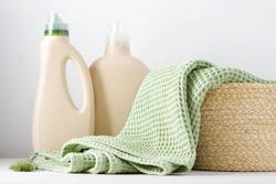 Clean blanket in white wicker basket filled with eco-friendly washing beggar bottles. Eco-friendly laundry concept