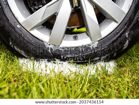Clean car wheel rim after washing with car shampoo, foam on the grass. Car wash in nature and summer cottage Stock fotó ©
