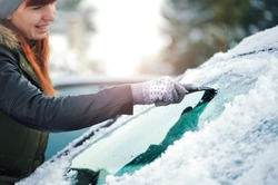 Clean car window from snow in winter time. Windshield cars cleaning. Removing snow from windows.