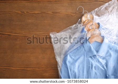 Clean clothes after dry-cleaning on table