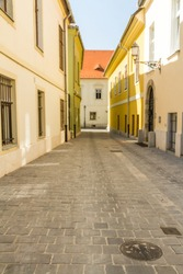 Clean cobbled old street in the morning, bright sunshine. Budapest, Hungary, portrait, wide angle.