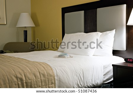 Clean, comfortable bed in modern hotel room with book and reading glasses