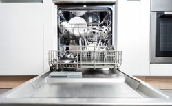 Clean dishes in dishwasher machine after washing, front view