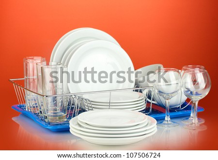 clean dishes on stand on red background