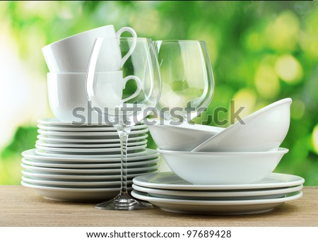 Clean dishes on wooden table on green background