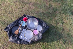 Clean dishes, pan, spoon, cup on a black bag and drying in the sun after eating a meal on a camping at natural forest park. Copy space, Selective focus.