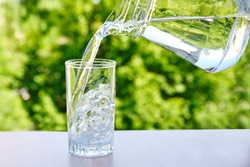 Clean drinking water is poured from a jug into a glass  on a wooden table  on a green nature outdoors background .