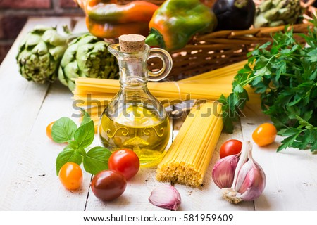 Clean eating concept, healthy mediterranean diet, ingredients for Italian meal, spaghetti, tomatoes, basil, olive oil, garlic, peppers, artichokes, on wood kitchen table, outdoors #581959609