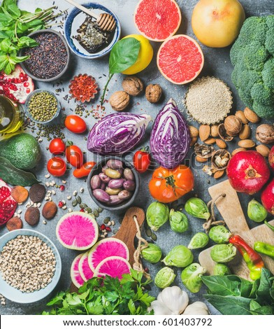 Clean eating concept over grey concrete background, top view. Vegetables, fruit, seeds, cereals, beans, spices, superfoods, herbs for vegan, gluten free, allergy-friendly weight loosing or raw diet