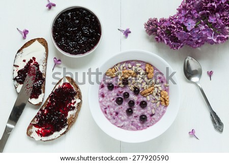 Clean eating diet healthy breakfast. Oatmeal porridge muesli with nuts, sunflower seeds, berries and berry jam. Two toasts with butter and jam. Served on white kitchen table background with lilac