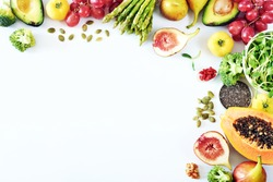 Clean-eating food frame with copy space. Top view of papaya, avocado, tomato, grape, asparagus, figs, broccoli, goji, chia, pumpkin seeds on white background.