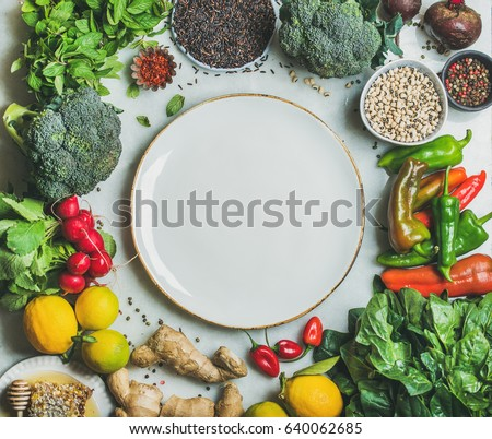 Clean eating healthy cooking ingredients. Vegetables, beans, grains, greens, fruit, spices over grey marble background, white plate with copy space in center, top view. Diet food concept Food frame