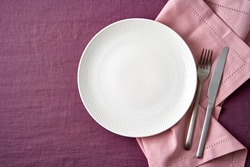 Clean empty white plate, fork and knife on bright blueberry red linen tablecloth on table, pink napkin copy space, mock up, top view. Concept for menu with cutlery