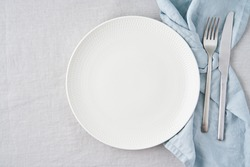 Clean empty white plate, fork and knife on pastel grey linen tablecloth on table, copy space, mock up, top view. Concept for menu with utensil