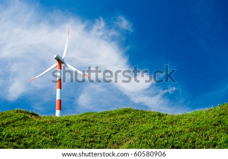 clean energy concept.  wind turbine in green hill under cloudy blue sky.