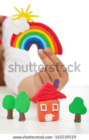 Clean environment concept - child hand holding colorful figures made of clay