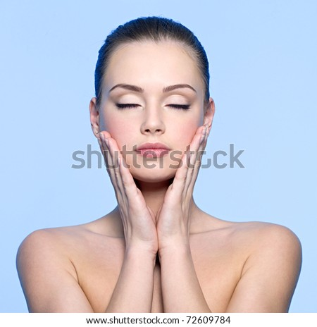 Clean face of beautiful teen girl touching her cheeks. Pretty young female with closed eyes