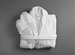 Clean folded bathrobe and slippers on grey background, top view