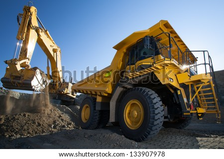 clean image of yellow excavator loading soil on a truck at mine back lit