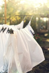 Clean laundry white clothes hanging on washing line and drying by sunshine in the wind in garden outdoor. Solar energy. Yard landscape background. Clothespin on rope. Ecological way to do housework