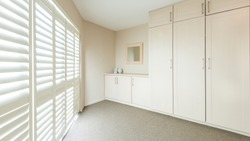 Clean minimal dressing area with tall cupboards and window shutters, carpet floor, neutral color and tones