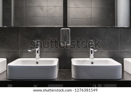 Clean new public toilet room empty. Two sinks and soap tank