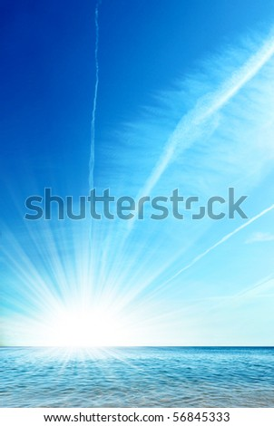 Clean ocean and bright blue sky with sun shining