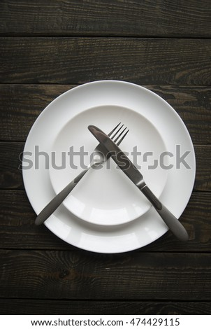 Clean plate with knife, fork and napkin on wooden background. #474429115
