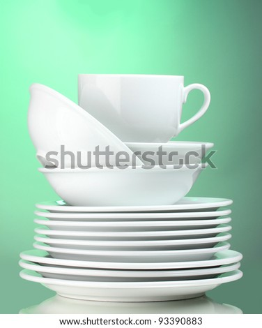 Clean plates and cup on green background