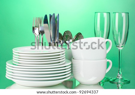 Clean plates, glasses, cups and cutlery on green background