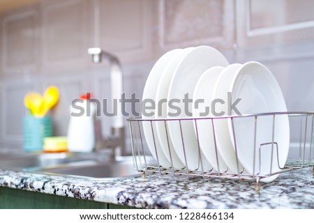 Clean plates in dish drying rack on the table on kitchen counter. Washing dirty dishes #1228466134