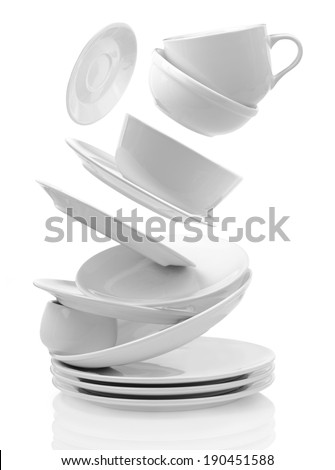 Clean plates, serving dishes and cups isolated on white