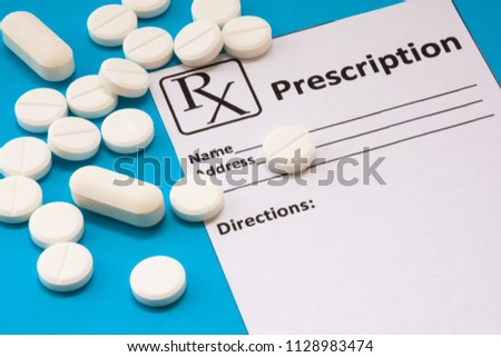 Clean recipe for prescription drug statement is near scattered white pills and tablets on a blue background. Pharmacological or medical concept photo to refer to prescription medicines for patients