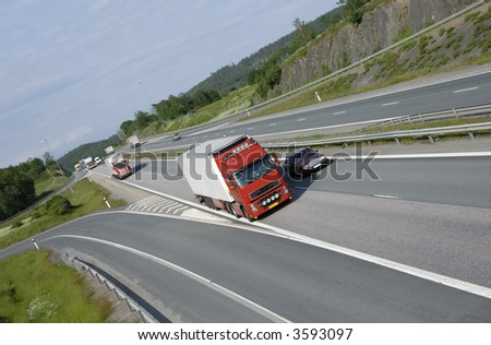 clean red truck driving on highway with country scenery in background