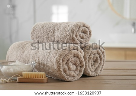 Clean rolled towels, cosmetic salt and brush on wooden table in bathroom