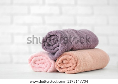 Clean rolled towels on table against white brick wall #1193147734